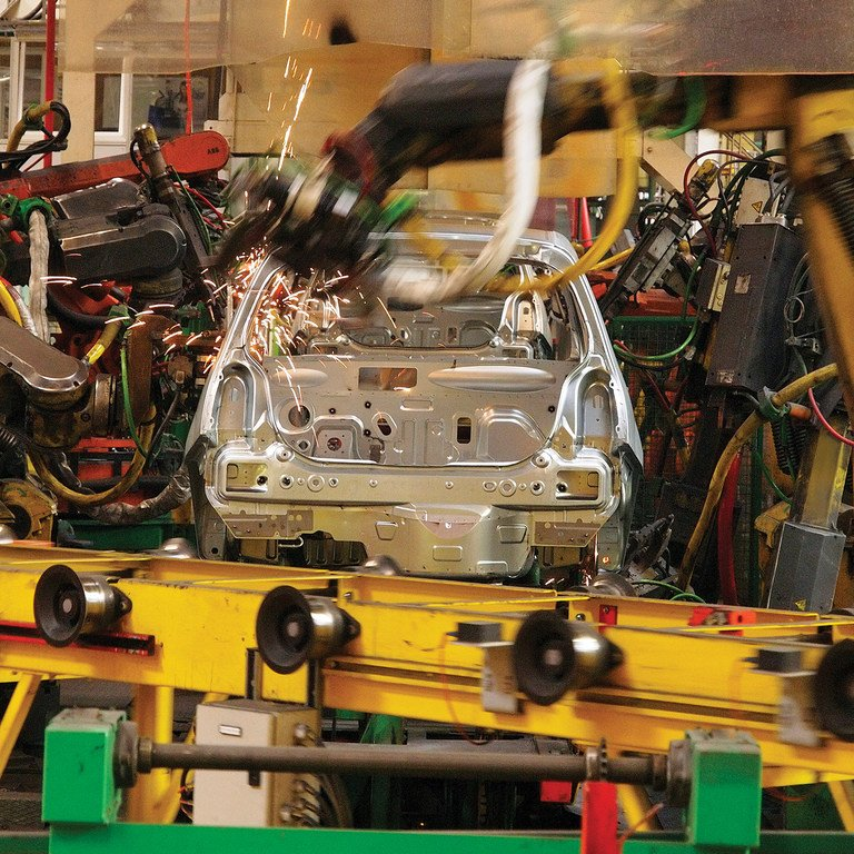 Robots building car on a moving conveyor